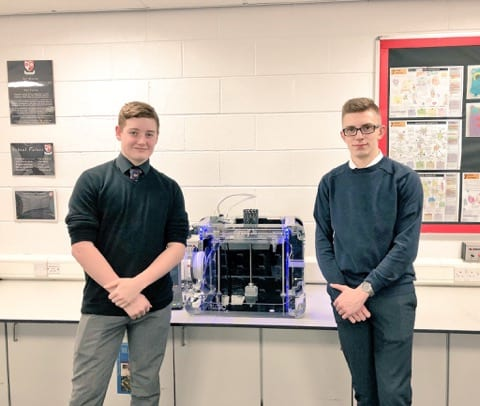two students next to a 3D printer