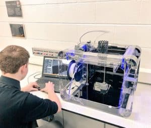 student at a laptop in front of a 3D printer